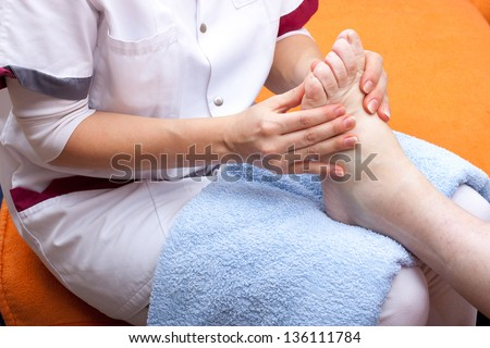 pretty  Nurse treats a patient's foot - stock photo