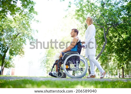 Pretty nurse walking with male patient in a wheelchair in park - stock photo