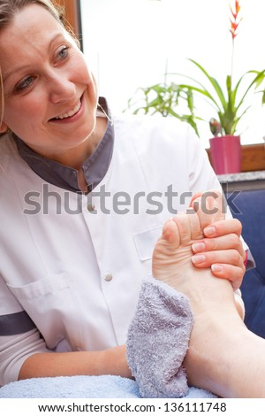 pretty Nurse washes the feet of an elderly  patient - stock photo