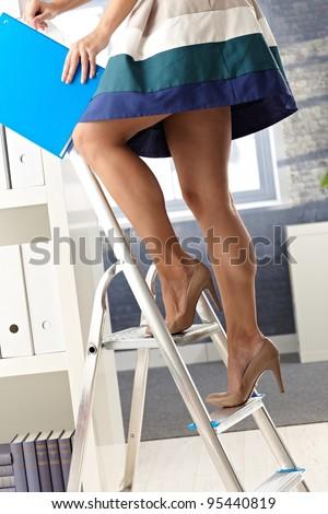 Pretty office assistant in short skirt standing on ladder, organizing file folder.? - stock photo