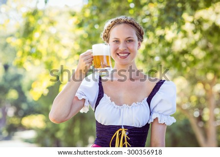 Pretty oktoberfest blonde toasting in the park on a sunny day - stock photo