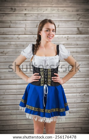 Pretty oktoberfest girl with hands on hips against wooden planks background - stock photo