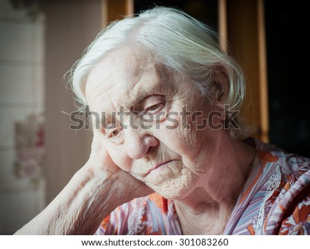 Pretty old grandmother sitting alone thinking cute - stock photo