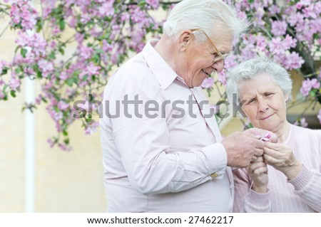 pretty old pair hold in hands small flower; outddor - stock photo