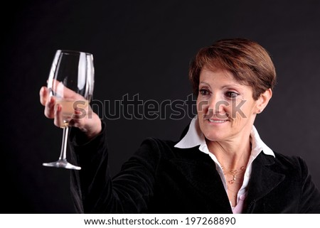 pretty old woman rising up a glass of wine and watching it (focus on the face) - stock photo