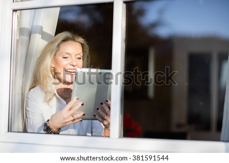 Pretty older blond woman sitting at the window with her tablet and relaxing in the sun - stock photo