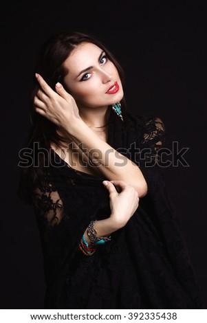 Pretty oriental woman in abaya on black background - stock photo