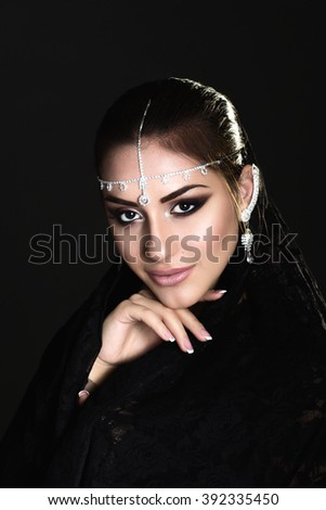 Pretty oriental woman in abaya on black background - stock photo
