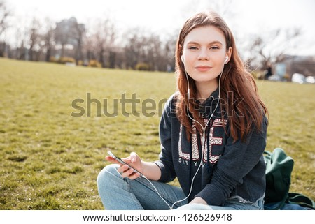 Pretty peaceful young woman listening to music from mobile phone on the lawn - stock photo