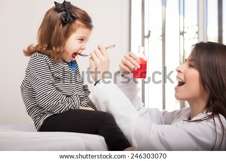 Pretty pediatrician giving some cough syrup to a little girl in her office - stock photo