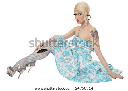 Pretty pierced and tattooed blond girl in vintage dress sitting on white background with big tropical butterfly on her leg - stock photo