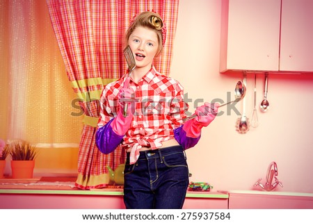 Pretty pin-up girl teenager cooking on a pink kitchen. Beauty, youth fashion. Pin-up style. - stock photo