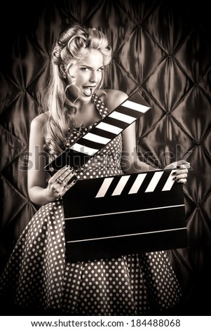 Pretty pin-up woman with retro hairstyle and make-up posing with clapper board over vintage background. Black-and-white photo. - stock photo