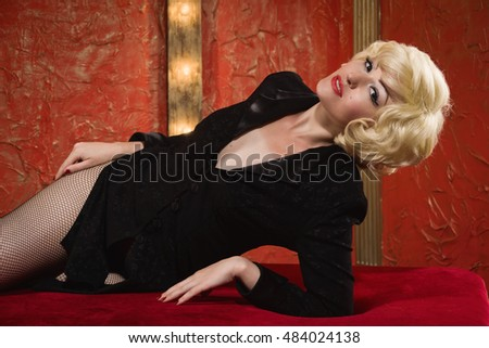 Pretty pinup blond model posing in a red room