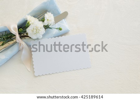 Pretty Place Setting has pastel blue napkin, Name Card, White Carnations and silverware on Off White Tablecloth Background with room or space for copy, text, your words. Horizontal aerial, above view