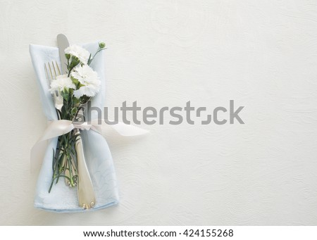 Pretty Place setting with Silverware, pastel blue napkin, and carnation flowers on textured cream white tablecloth as background with room or space for copy, text, your words.  Horizontal aerial view