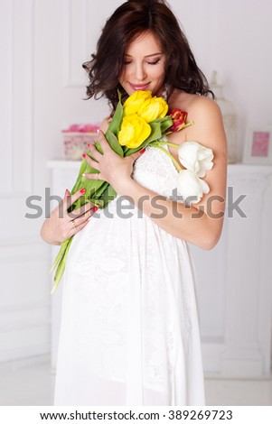 Pretty pregnant girl is holding tulip flowers