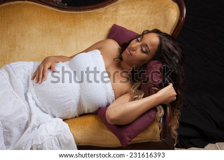 Pretty pregnant woman in a white dress reclining on a gold couch and holding her belly with a pleased smile,