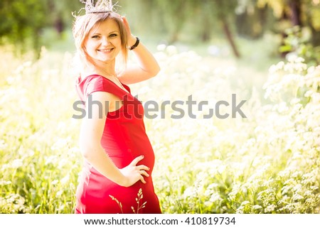 Pretty pregnant woman in red posing in green park. Young woman holding her tummy - stock photo