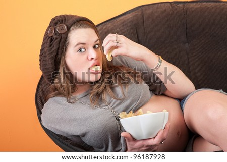 Pretty pregnant woman resting on couch eats potato chips