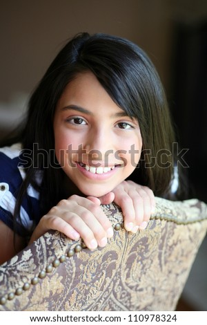 pretty preteen ethnic girl sitting in chair
