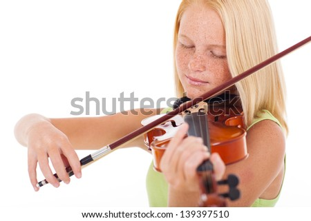 pretty preteen girl playing violin over white background - stock photo