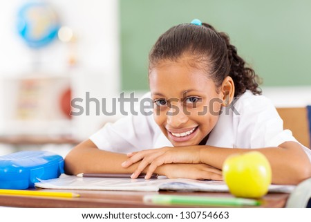 pretty primary schoolgirl sitting in classroom
