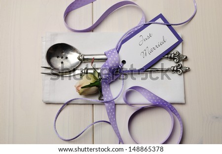Pretty purple polka dot wedding table place setting on white shabby chic table with Just Married tag. - stock photo