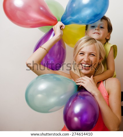 pretty  real family with color balloons on white background, blond woman with little boy at birthday party