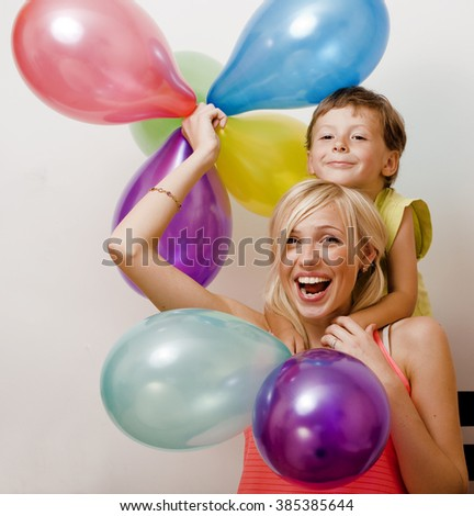 pretty real family with color balloons on white background, blond woman with little boy at birthday party bright smiling mother