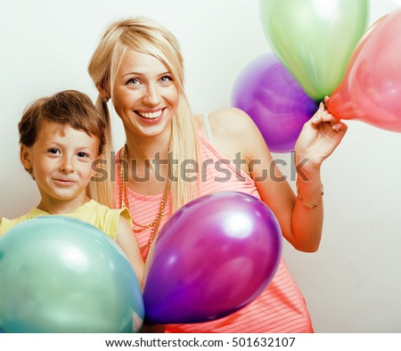 pretty real family with color balloons on white background, blonde mother with cute son on birthday party celebration, lifestyle people concept