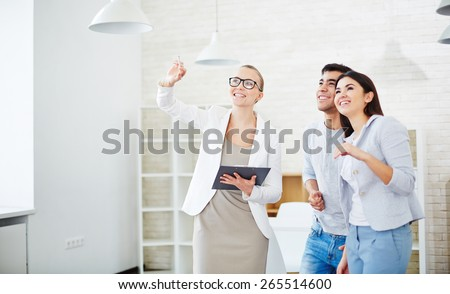 Pretty realtor showing new flat to young couple - stock photo