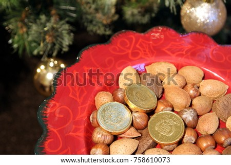 Pretty red Christmas plate with traditional festive almonds, hazelnuts and Brazil nuts, and chocolate money,with a Christmas tree in the background