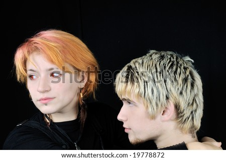 Pretty red-eyed vampire girl and a young guy, on black background