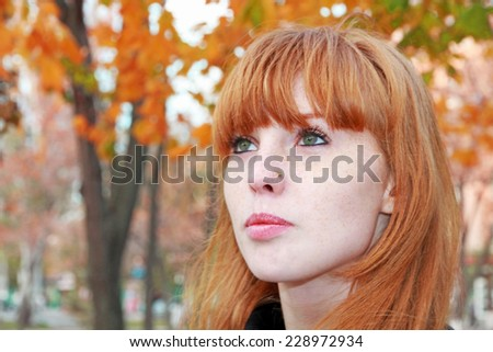 Pretty red hair girl face with freckles against red autumn foliage. - stock photo