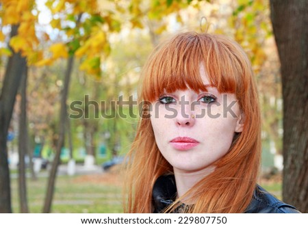 Pretty red hair girl with freckles looks at camera. - stock photo