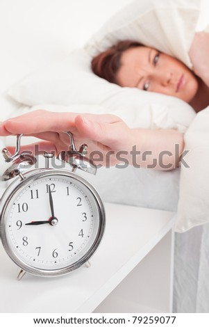 Pretty red-haired female waking up thanks to an alarm clock in the bedroom - stock photo