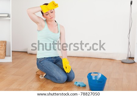 Pretty red-haired woman having a break while cleaning the floor at home - stock photo