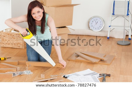 Pretty red-haired woman using a saw for diy at home - stock photo