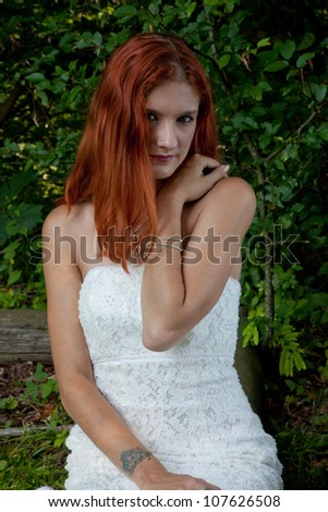 Pretty redhead bride in her wedding dress, sitting outside on a log in a grassy field, looking at the camera with a thoughtful expression
