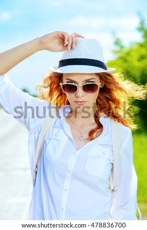 Pretty redhead girl in white summer clothed standing outdoor. Summer day.