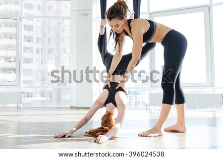 Pretty redhead girl practicing aerial yoga with personal trainer in studio - stock photo