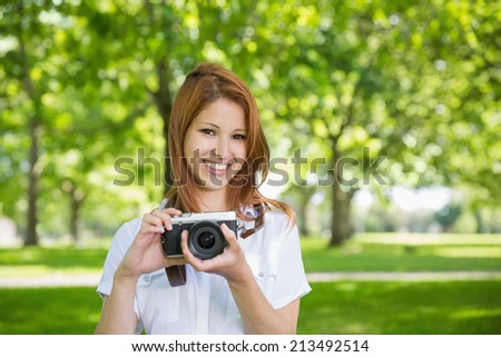 Pretty redhead holding her camera in the park on a sunny day - stock photo