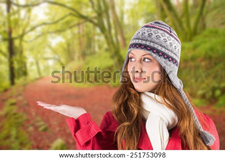 Pretty redhead in warm clothing against peaceful autumn scene in forest