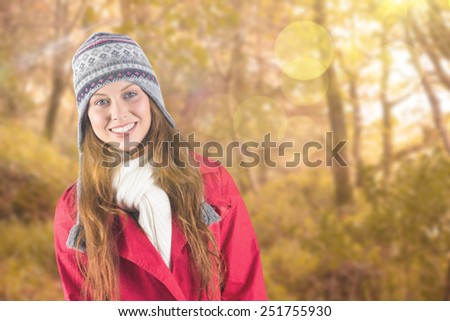 Pretty redhead in warm clothing against tranquil autumn scene in forest