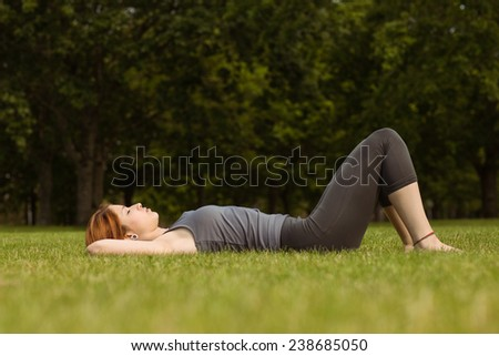 Pretty redhead lying on grass in park - stock photo