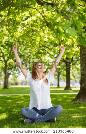 Pretty redhead raising her arms in the park on a sunny day