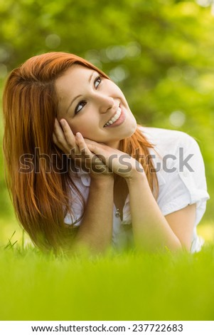 Pretty redhead smiling and lying on grass in park