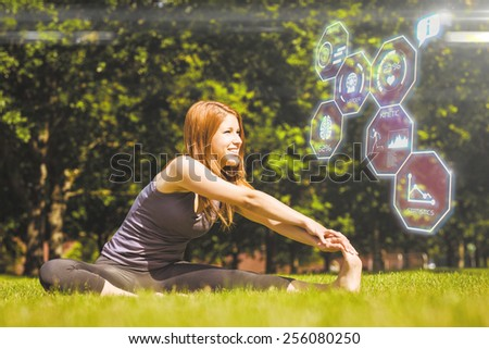 Pretty redhead smiling stretching in park against fitness interface - stock photo