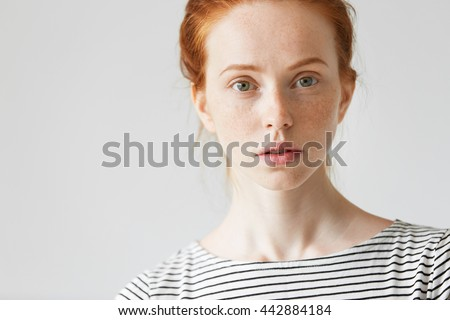 Pretty redhead student girl with freckles wearing sailor shirt against white studio wall background with copy space for your text or promotional content, looking with serious and concerned expression - stock photo